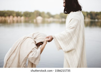 A shallow focus shot of a female grabbing the hand of Jesus Christ for healing and help