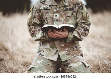 A shallow focus shot of a young soldier kneeling while holding a bible in a field
