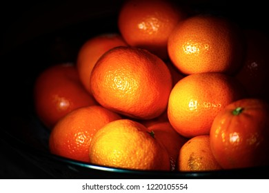 A shallow focused shot of a bowl of bright orange tangerines against a dark background.