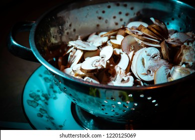 A shallow focused shot of a bowl of freshly cut mushrooms highlighted in a metal cauldron  sitting on a ceramic plate on a wooden table.