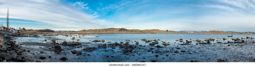 Shallow and muddy coastline of Hafrsfjord fjord with scattered stones and rocks, Tananger, Norway, March 2018