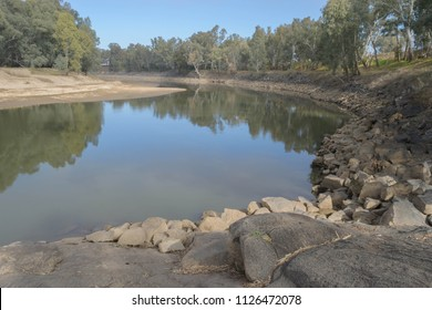a shallow murrumbidgee river with sandy beach and rock barrier on the sides and tree reflection in the water on a sunny day