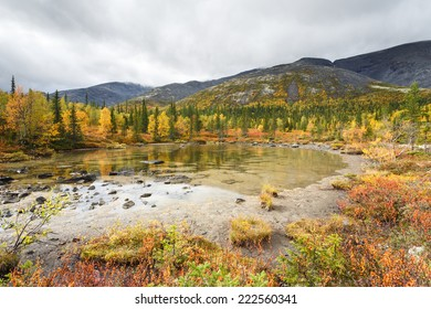 Shallow Polygonal lake surrounded by greenery with mountain ridge reflection