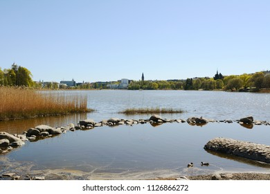 Shallow pool at the edge of Toolo bay, Helsinki, marked by rocks and reeds. City buildings stand on the opposite shore.
