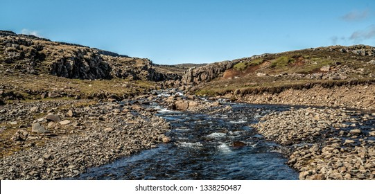 Shallow river stream nature terrain in countryside. Four-wheel drive vehicle track.