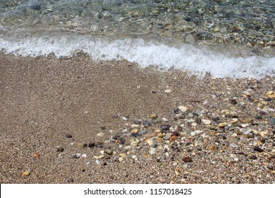 Shallow sea water on beach with sand pebbles swash wave waterline