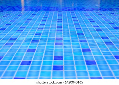 shallow wadding pool water in swimming pool. pool design with small ceramic tiles. repeating dark deep blue tiles dotted lighter shade of blue floor tiles. deeper level in the background.