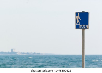 Shallow water sign on the beach in Croatia and wavy sea in background. Vacations, travel, swimming and safety concepts