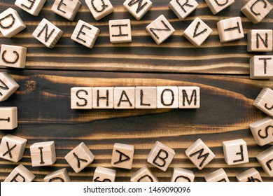Shalom - word from wooden blocks with letters, Jewish greeting or saying goodbye concept, random letters around, top view on wooden background