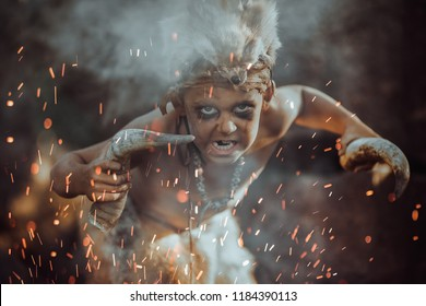 Shaman boy at the fire. Close up of scary young primitive boy outdoors near bonfire. Witch craft concept. Angry caveman, manly boy with horns near bonfire. Prehistoric tribal man outdoors on nature