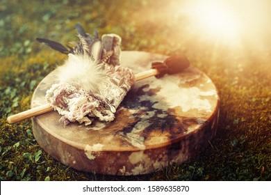 shamanic drum and shamanic feathers on denim.
