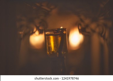 Shamash oil candle on the background of Chanukkah menora blurred flames in a decorative glass box, Hanukkah concept, dark background with copy space