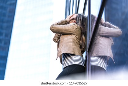 Shame, failure, making mistakes and embarrassment concept. Depressed and hysterical woman crying in city. Embarrassed person covering face with hands. Workplace bullying or problems at work.