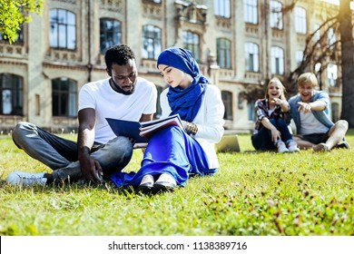 Shame on them. Multicultural groupmates discussing their homework while sitting outdoors and ignoring young people fingering toward them in the background.