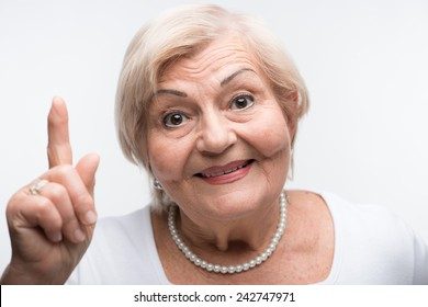 Shame on you. Closeup portrait of elderly woman waving her finger with smile while standing against white background