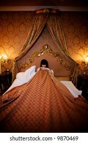 shamed girl in bed covering herself