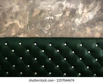 shameless beautiful vintage dark leather cushion sofa, background of white buttoned on luxury green leather pattern and concrete wall, Vip luxury green leather with cement wall, loft style background