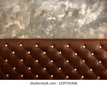 shameless beautiful vintage dark leather cushion sofa, background of white buttoned on luxury brown leather pattern and concrete wall, Vip luxury brown leather with cement wall, loft style background