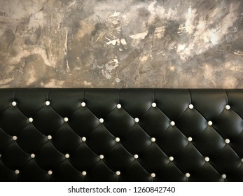 shameless beautiful vintage dark leather cushion sofa, background of white buttoned on luxury black leather pattern and concrete wall, Vip luxury black leather with cement wall, loft style background