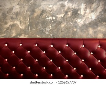shameless beautiful vintage dark leather cushion sofa, background of white buttoned on luxury red leather pattern and concrete wall, Vip luxury red leather with cement wall, loft style background
