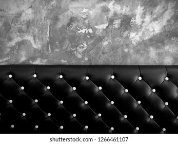 shameless beautiful vintage dark leather cushion sofa, background of white buttoned on luxury black leather pattern and concrete wall, Vip luxury black leather with cement wall, monochrome background