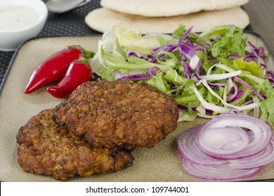 Shami Kebabs - A couple of spicy lamb kebab patties served with mint raita dip, red chillies, crunchy salad, pitta bread and raw red onions. Close up.