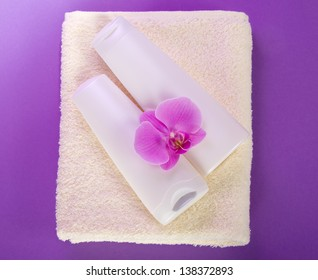 Shampoo and balm conditioner on a terry towel, with an orchid flower on the violet