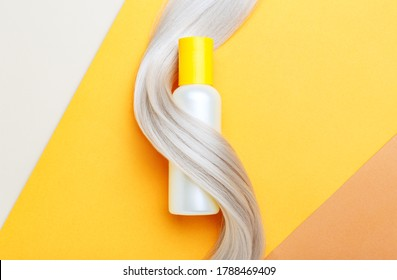 Shampoo bottle mockup strand in lock curl of blonde hair on orange color background. Yellow bottle shampoo. Flat lay copy space. Hair care cosmetics bath beauty products hair treatment