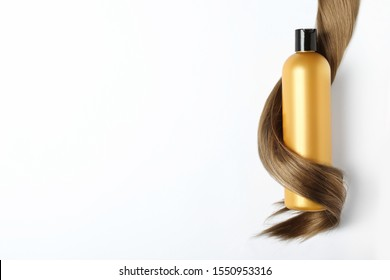 Shampoo bottle wrapped in lock of hair isolated on white, top view. Natural cosmetic products