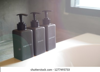 Shampoo, shower gel and hair conditioner in black ceramic pump bottles on the bathtub near the  window with brightness flare. (Hotel amenities)