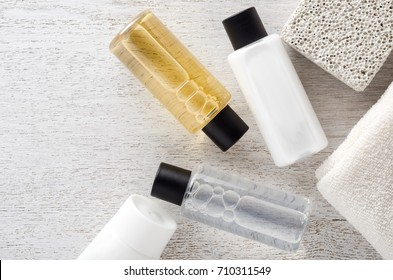 Shampoo and shower gel with towel on a table