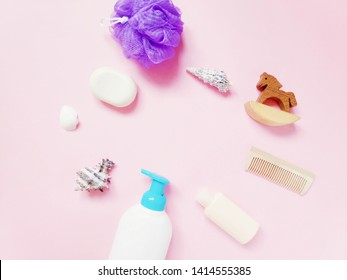 Shampoo, soap, purple puff sponge and toy wooden horse on a pink background. Flat lay beauty photo