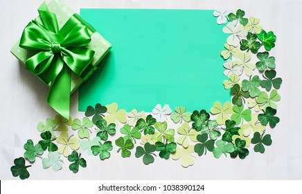 shamrock frame for Patrick day and green festive gift box on white wood background