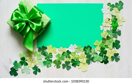 shamrock frame for Patrick day  and green festive  gift box on white wood background. top view