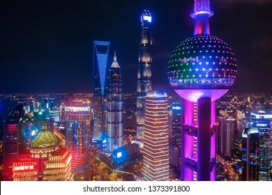 Shanghai, China - 04/18/2019 : Aerial view of The Pearl in Downtown. Financial district and business centers in smart city in Asia. Top view of skyscraper and high-rise buildings at night.