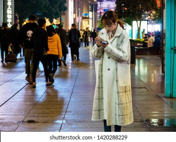 SHANGHAI, CHINA - 12 MAR 2019 –An attractive young Chinese lady on her smartphone at East Nanjing Road (Nanjing Dong Lu) pedestrian street