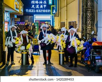 SHANGHAI, CHINA - 12 MAR 2019 – Middle aged women street vendors peddle Pokemon merchandise along East Nanjing Road (Nanjing Dong Lu) pedestrian street in the evening