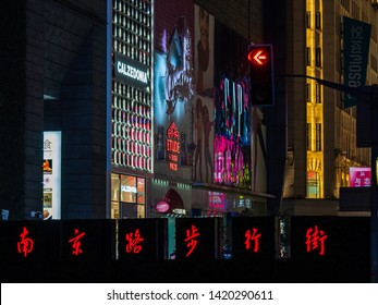 """SHANGHAI, CHINA - 12 MAR 2019 – Chinese signage displaying the words """"Nanjing Road Pedestrian Street"""" at the end of the East Nanjing Road (Nanjing Dong Lu) in the evening."""