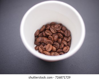 Shanghai, China - 14 October 2016: Coffee beans in a paper cup on a grey table