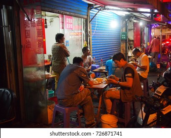 Shanghai, China - 14 October 2016: Colourful street food stall on a busy road at night