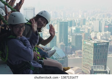 Shanghai/ China - 7th April 2019: Close up of people in harnesses sitting on the skywalk on the outside of Jin Mao Tower, one of Shanghai's tallest buildings on a polluted day