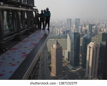 Shanghai/ China - 7th April 2019: People in harnesses walking on the skywalk on the outside of Jin Mao Tower, one of Shanghai's tallest buildings on a polluted day