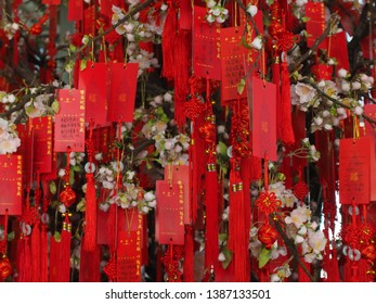 Shanghai/ China - 7th April 2019: Red devotions and pink blossom in a tree inside the Jin Mao Tower during the Qing Ming (Grave sweeping) festival