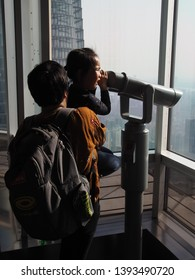 Shanghai/ China - 7th April 2019: Mother and child using a telescope on the viewing deck on Jin Mao Tower with the Shanghai Tower in the background in the financial district of Shanghai (Lujiazui)