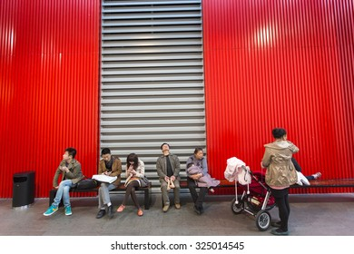 SHANGHAI, CHINA, APRIL 2: Group of People sitting down on red benches at the new Modern Art Museum in Shanghai, China 2 April 2013