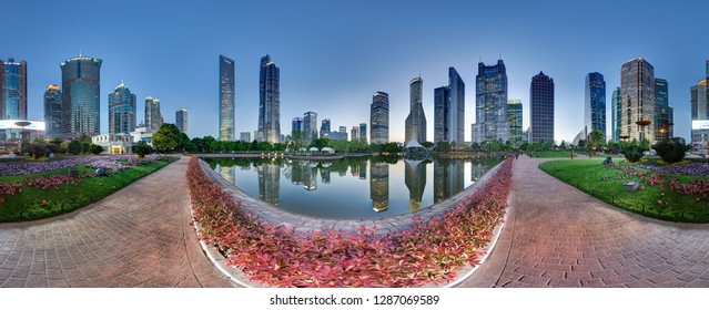 SHANGHAI, CHINA - APRIL 21, 2015: 360 degrees skyline of Pudong financial center by night with green park. Famous SWFC, Jin Mao & partially hidden Shanghai's towers are visible in water reflection.