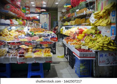 Shanghai, China - April 27, 2019: A retailer sits at a market fruit store.