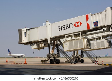 Shanghai, China - Aug 21, 2019: A jet bridge with the HSBC logo at the busy Shanghai Pudong Airport, with several airplanes lining up on the runway for departure in the background.