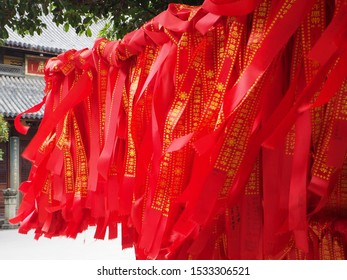 Shanghai/ China - August 25th 2019: Red prayer ribbons with gold Chinese characters on them tied in a sacred tree in Longhua Temple, with the ribbons blowing in the wind