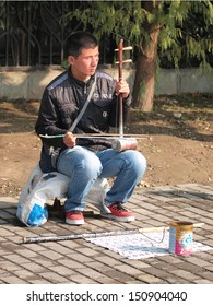 SHANGHAI, CHINA - CIRCA NOVEMBER 2012 : A blind Man plays music instrument to earn a living outside of Centry Park in Shanghai circa November 2012.